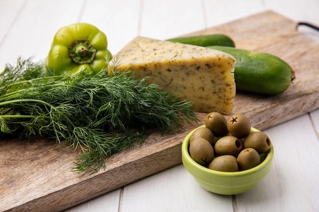Vue latérale du fromage avec des concombres aux poivrons sur un support avec des olives sur une plaque blanche