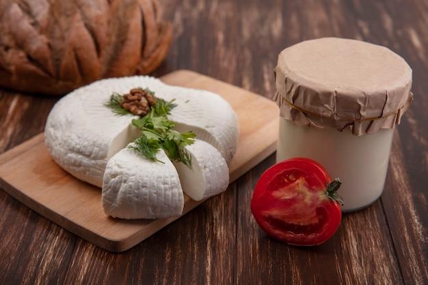 Vue latérale du fromage feta sur un support avec tomate et yaourt dans un pot sur un fond de bois