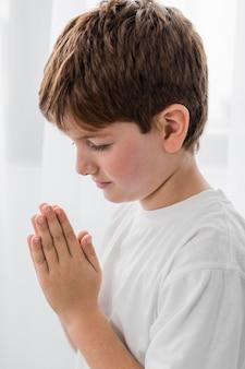 Vue latérale du garçon priant