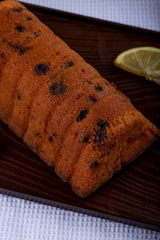 Vue latérale du gâteau aux raisins secs avec des tranches de citron sur une planche de bois