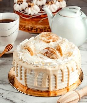 Vue latérale du gâteau blanc décoré de crème fouettée au chocolat blanc fondu et de bananes sur la table