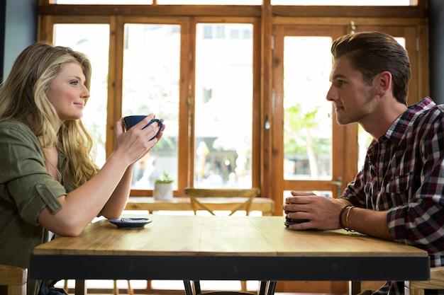 Vue latérale du jeune couple aimant prendre un café à la cafétéria