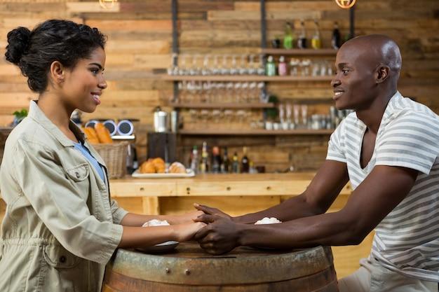 Vue latérale du jeune couple aimant se tenant la main à table dans un café