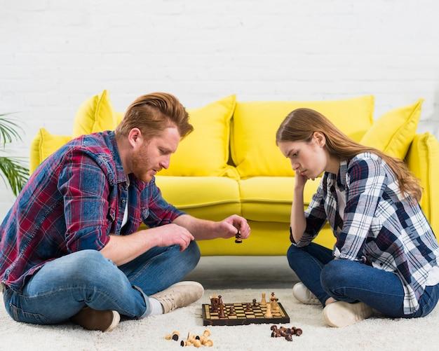 Vue latérale du jeune couple assis sur un tapis blanc jouant le jeu d'échecs