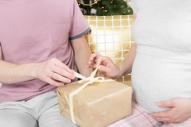 Vue latérale du jeune couple ouvrant la boîte de cadeau de noël.