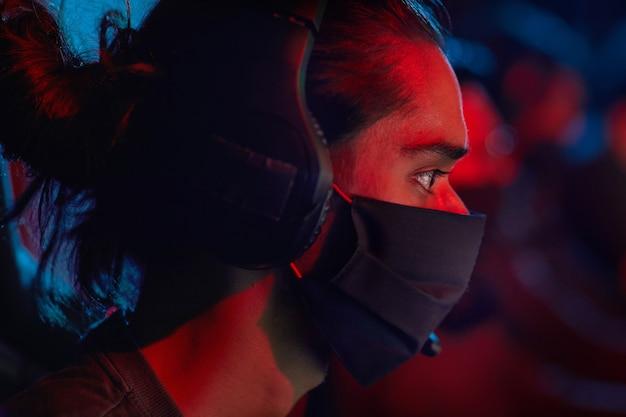 Vue latérale du jeune hacker dans les écouteurs et dans un masque de protection à l'aide d'un ordinateur au travail