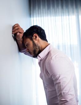 Vue latérale du jeune homme d'affaires réfléchi, debout contre le mur