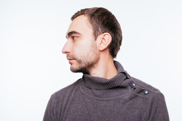 Vue latérale du jeune homme barbu isolé sur mur gris