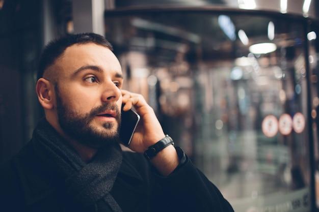 Vue latérale du jeune homme barbu, vêtu de vêtements incasual, il est debout dans la rue et à l'aide d'un smartphone