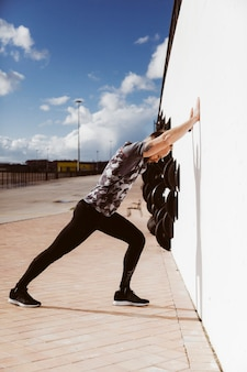 Vue latérale du jeune homme sportif, faire des tractions sur le mur