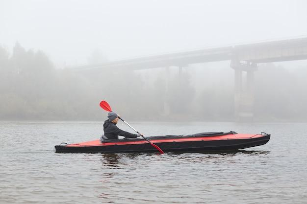 Vue latérale du jeune kayakiste en rivière, rembourrage