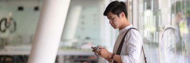Vue latérale du jeune photographe masculin vérifiant sa photo sur un appareil photo numérique