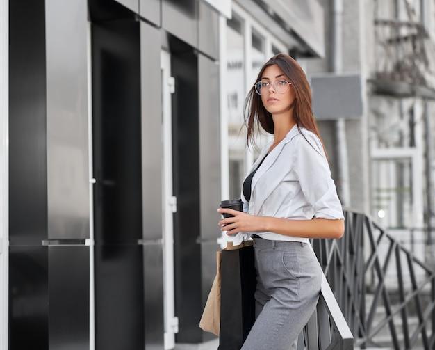 Vue latérale du joli modèle posant debout près de la boutique, des sacs et du café.