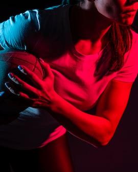 Vue latérale du joueur de rugby féminin tenant le ballon