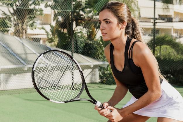 Vue latérale du joueur de tennis concentré