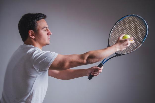 Vue latérale du joueur de tennis posant avec raquette et balle