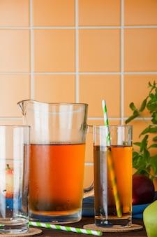 Vue latérale du jus de pomme froid dans le tableau sur fond de carreaux orange. espace vertical pour le texte