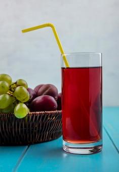 Vue latérale du jus de raisin noir avec tube à boire en verre et panier de raisin pluots sur surface bleue et fond blanc