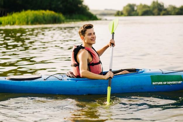 Vue latérale du kayakiste mâle kayak sur le lac