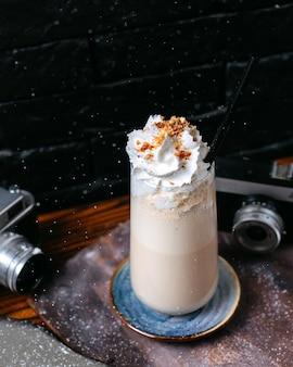 Vue latérale du lait frappé à la crème fouettée en verre sur table en bois