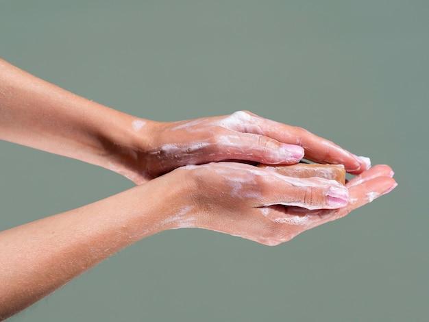 Vue latérale du lavage des mains avec du savon