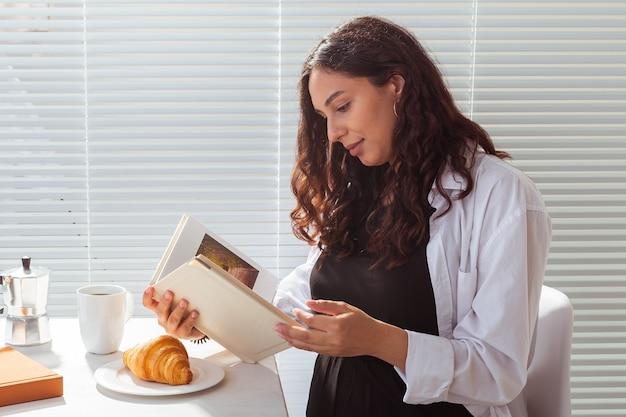Vue latérale du livre de lecture de bonne jeune femme heureuse tout en prenant le petit déjeuner le matin avec du café et