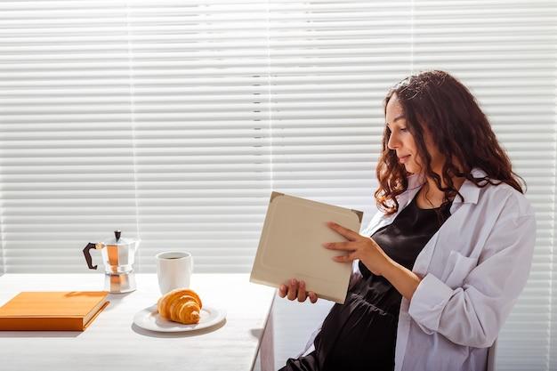 Vue latérale du livre de lecture de femme enceinte heureuse tout en prenant le petit déjeuner avec café