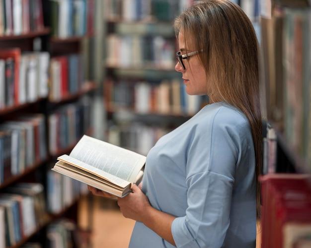 Vue latérale du livre de lecture de femme
