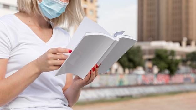 Vue latérale du livre de lecture de masque médical à l'extérieur de la femme