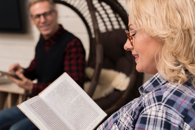 Vue latérale du livre de lecture de la mère avec le père défocalisé