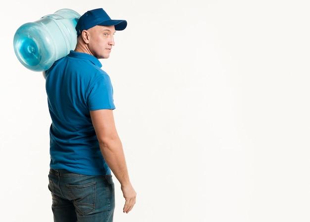 Vue latérale du livreur transportant une bouteille d'eau