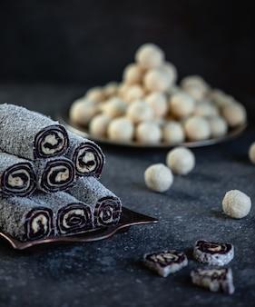 Vue latérale du lukum traditionnel turc avec des flocons de noix de coco sur un plateau sur le mur noir