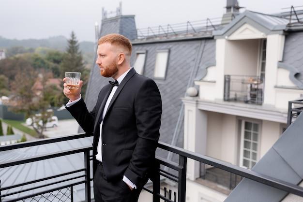 Vue latérale du marié aux cheveux roux boit du whisky sur le balcon du matin du mariage