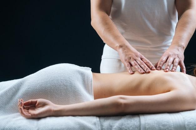 Vue latérale du masseur masculin massant le dos d'une jeune femme allongée sur une table de massage sur fond noir