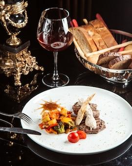 Vue latérale du médaillon de boeuf grillé avec sauce et légumes sur une plaque blanche sur la table