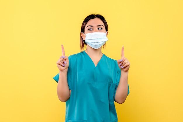 Vue latérale du médecin dans un masque parle de l'importance du lavage des mains
