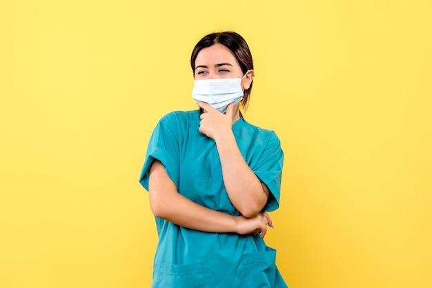 Vue latérale du médecin dans un masque pense aux symptômes du covid
