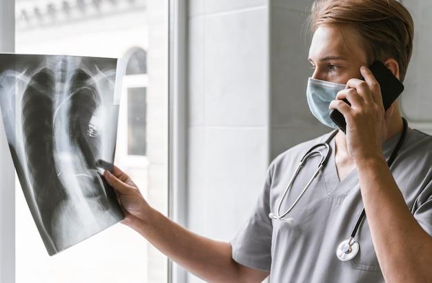 Vue latérale du médecin regardant la radiographie et parler au téléphone