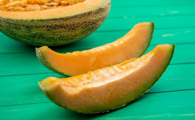 Vue latérale du melon cantaloup délicieux et tranché sur une surface en bois vert