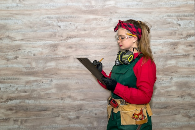 Vue latérale du menuisier femme prenant des notes sur le presse-papiers