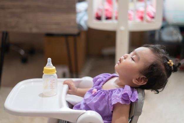 Vue latérale du mignon petit bébé asiatique assis endormi sur la table à manger après avoir mangé plein dans la maison
