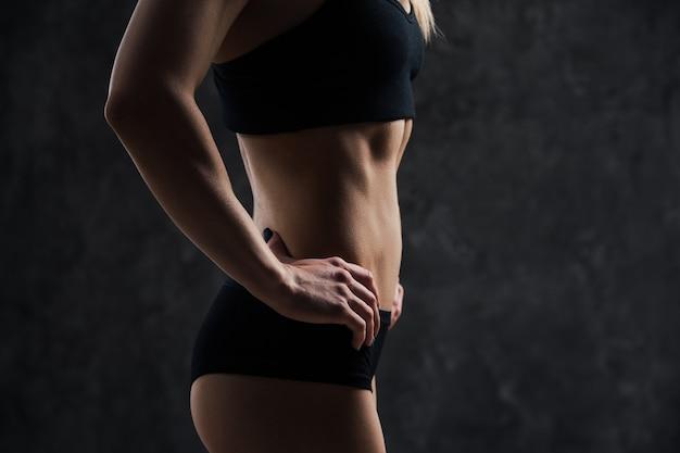 Vue latérale du modèle féminin de remise en forme musculaire debout