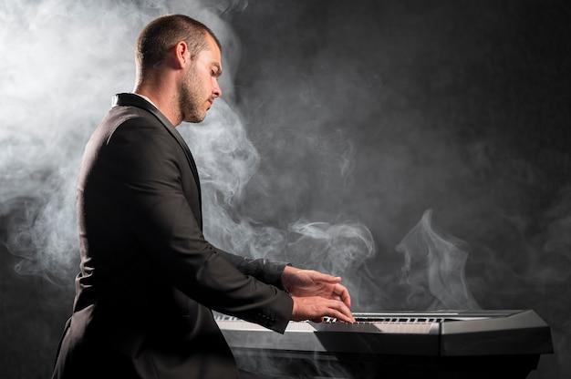 Vue latérale du musicien artistique et effet de fumée