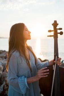 Vue latérale du musicien féminin avec violoncelle à l'extérieur au coucher du soleil