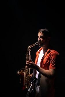 Vue latérale du musicien jouant du saxophone avec copie espace