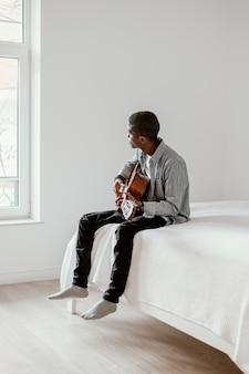 Vue latérale du musicien masculin avec guitare