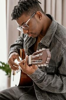 Vue latérale du musicien masculin jouant de la guitare à la maison
