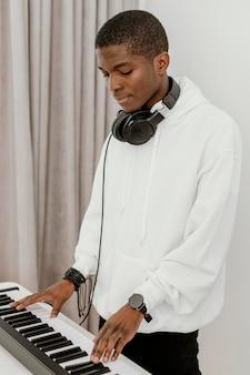 Vue latérale du musicien masculin à la maison à jouer du clavier électrique