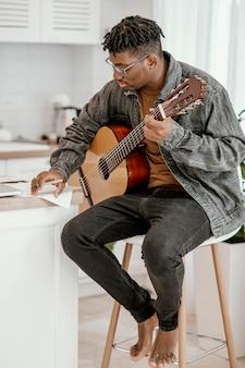 Vue latérale du musicien masculin à la maison à jouer de la guitare