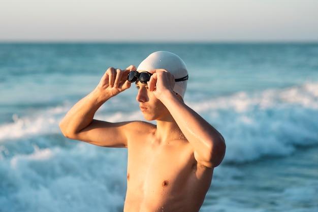 Vue latérale du nageur masculin posant tout en regardant le coucher du soleil sur la plage